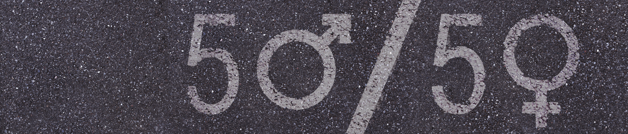"Asphalt with ""50/50"" written in chalk and the male and female symbols replace the ""0""."