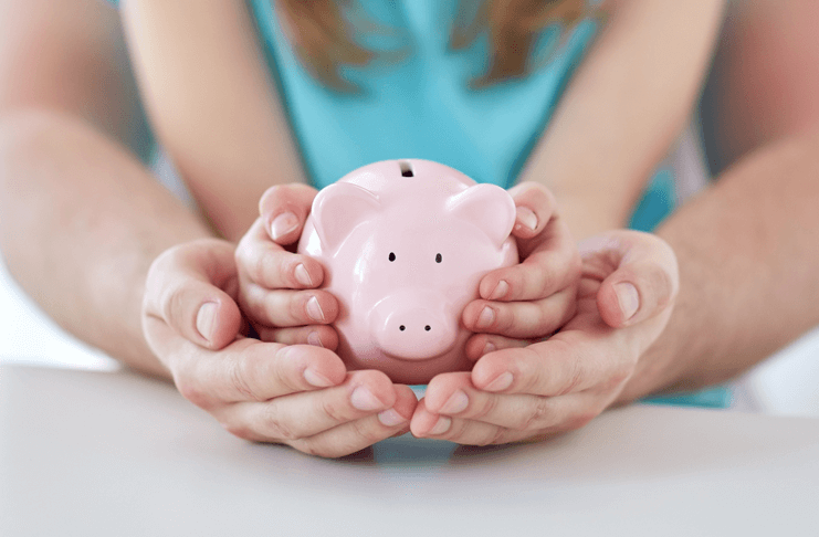 picture of adult and child hands holding piggy bank