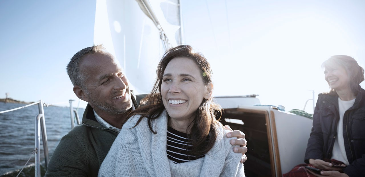 a couple on a sailboat smiling with the sun behind them